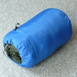 Sleeping bag rolled up in blue sack.